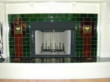 Fireplace using dark green tiles, dark brown tiles and two moulded lemon tiles to give weight to a horizontal designed fireplace. Note how the grout lines add to the overall design.