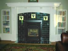 Dark green tiles laid like brick, with three decorative moulded tiles - Available from Charles Rupert Designs